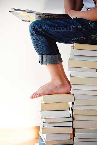 pies-desnudos-chica-en-vaqueros-sentada-sobre-tonga-de-libros-320x480px